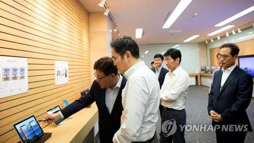 Samsung Electronics Vice Chairman Lee Jae-yong (2nd from L) looks at a display product during a visit to Samsung Display Co.'s factory in Asan, about 100 kilometers south of Seoul, on Aug. 26, 2019, in this photo released by Samsung Electronics. (PHOTO NOT FOR SALE) (Yonhap)