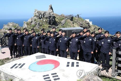 Coast guard members stationed on South Korea's easternmost Dokdo Islets salute the national flag while resolving to uphold the islets' defense one day ahead of Liberation Day on Aug. 14, 2019. (Yonhap)