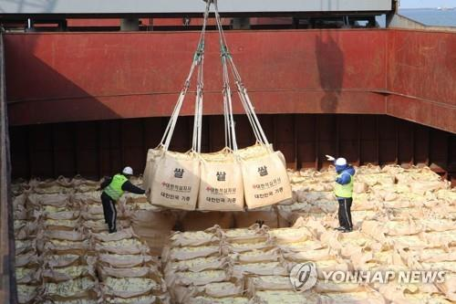 In this file photo, taken in 2010, South Korean workers in the southwestern port city of Gunsan load rice onto a vessel for shipment to North Korea. (Yonhap)