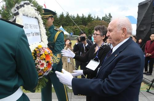 An international Korean War veteran offer flowers for fallen Korean War heroes buried at the UN Memorial Cemetery in Busan during a ceremony marking the 74th United Nations Day on Oct. 24, 2019. (Yonhap)