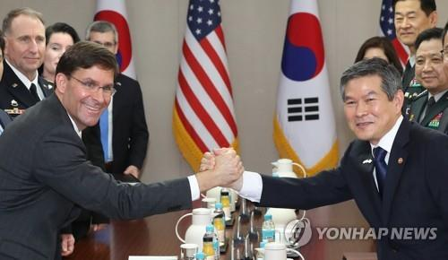 South Korean Defense Minister Jeong Kyeong-doo (R) and U.S. Secretary of Defense Mark Esper clasp hands during their talks at the defense ministry in Seoul on Aug. 9, 2019, in this file photo. (Yonhap)
