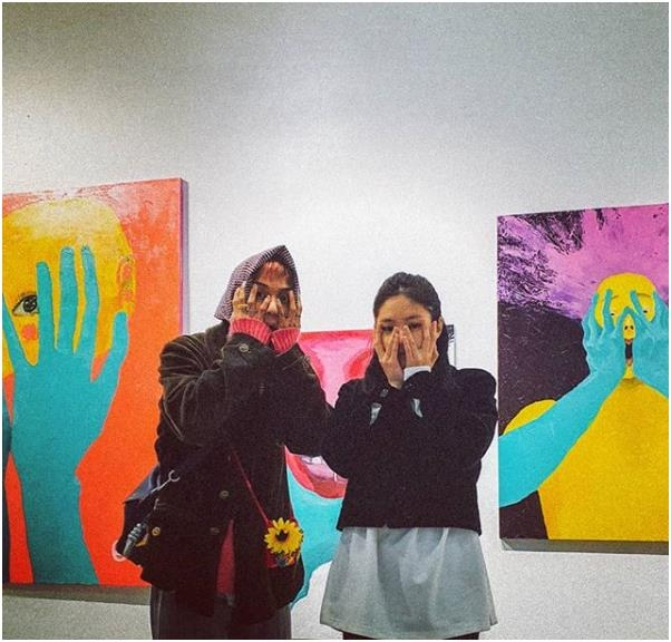 This photo of WINNER's Mino (L) next to BLACKPINK's Jennie taken against the backdrop of the former's paintings on exhibition is captured from Mino's Instagram account. (PHOTO NOT FOR SALE) (Yonhap)