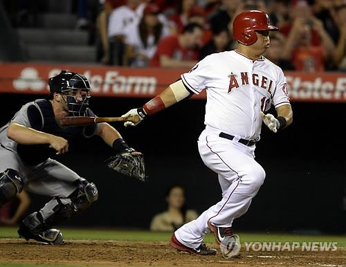 In this EPA file photo from July 18, 2014, Hank Conger of the Los Angeles Angels (R) hits an RBI single against the Seattle Mariners in the bottom of the fifth inning of a Major League Baseball regular season game at Angel Stadium in Anaheim, California. (Yonhap)