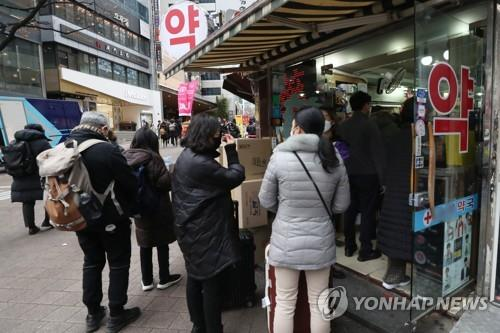 Foreign tourists line up to purchase facial masks at a drug store in Myeongdong, central Seoul, on Jan. 28, 2020. (Yonhap)