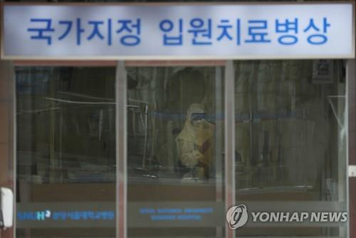 A staff member at Seoul National University Hospital in Bundang, south of Seoul, is in a full protective suit waiting to check people entering the entrance on Jan. 29, 2020. (Yonhap)