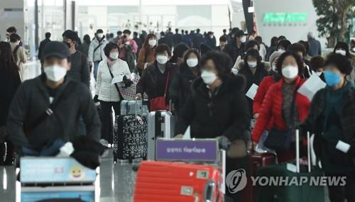 This undated file photo shows masked travelers arriving at Incheon International Airport, west of Seoul. (Yonhap)