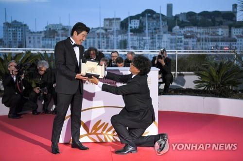 "This photo provided by the AFP shows South Korean director Bong Joon-ho (R) and actor Song Kang-ho posing with the trophy during a photo-call after winning the Palme d'Or for ""Parasite"" at the closing ceremony of the 72nd Cannes Film Festival on May 25, 2019. (Yonhap)"