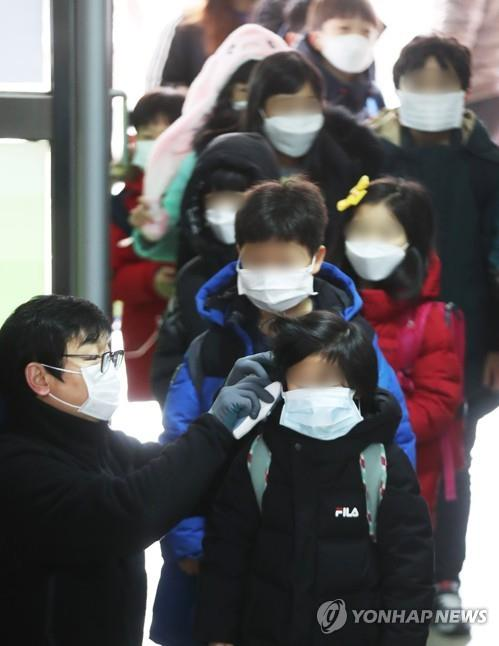 A teacher checks students' temperatures at an elementary school in Suwon, south of Seoul, on Jan. 29, 2020. (Yonhap)