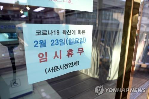 A notice in a store window shows that a Daegu market has temporarily closed to prevent the further spread of COVID-19 on Feb. 21, 2020. (Yonhap)