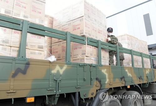 Soldiers are on a military truck to help distribute masks to the public on March 1, 2020, in this photo provided by the Ministry of Food and Drug Safety. They were among dozens of service members mobilized to help produce and deliver masks to the public as the country faced mask supply problems. (PHOTO NOT FOR SALE) (Yonhap)