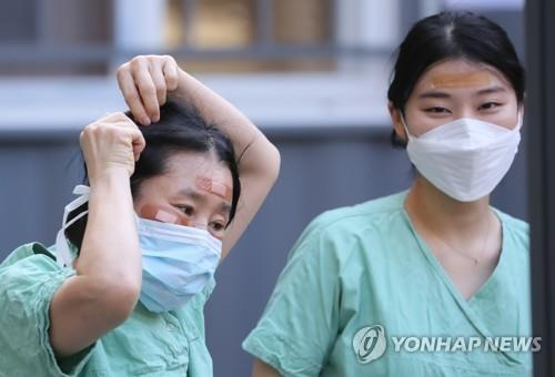 Medical staffers use band-aids to cover wounds on their faces caused by wearing protective goggles for long hours while treating coronavirus patients at Dongsan Hospital in Daegu, 300 kilometers southeast of Seoul, on March 4, 2020. (Yonhap)