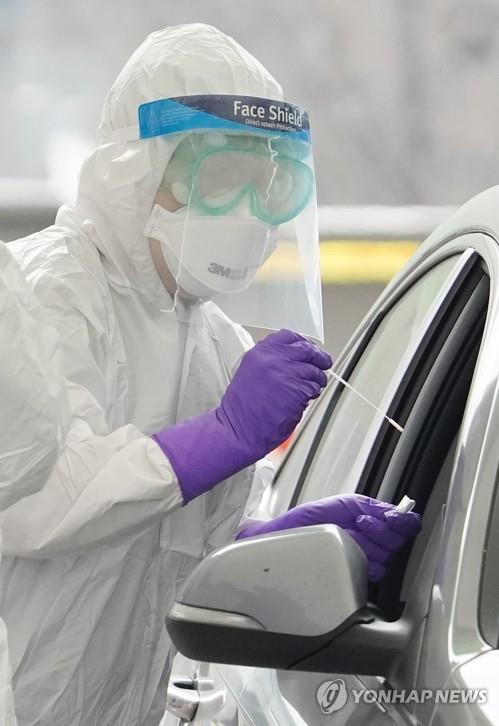 A medical worker collects a sample from a citizen in a car at a drive-thru clinic in front of Seoul Olympic Main Stadium on March 3, 2020, to test for the new coronavirus. (Yonhap)