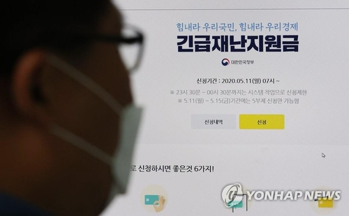 The undated photo shows a masked bypasser looking at an information poster about the government's emergency relief fund. (Yonhap)