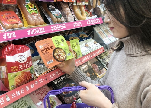 This undated photo, provided by the convenience store chain CU, shows a consumer looking at tofu at CU. (PHOTO NOT FOR SALE) (Yonhap)