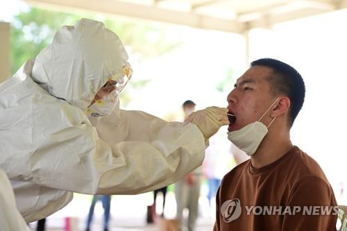 A medical official collects a sample from an enlistee for a coronavirus test upon joining the military at an Army boot camp on May 18, 2020, in this photo provided by the Army. (PHOTO NOT FOR SALE) (Yonhap)