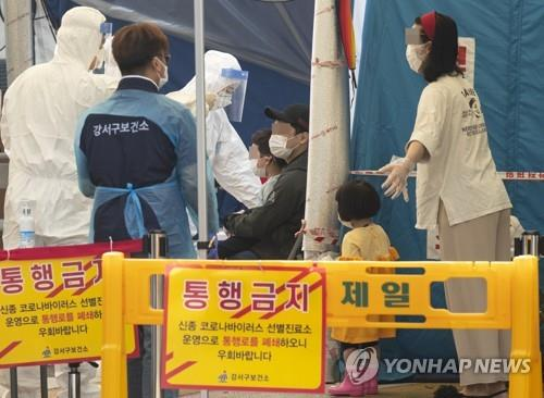 Health workers speak to citizens waiting in line for virus tests at a public medical center in Gangseo Ward, western Seoul, on May 26, 2020, one day after a kindergarten student in the district tested postive for the novel coronavirus. (Yonhap)