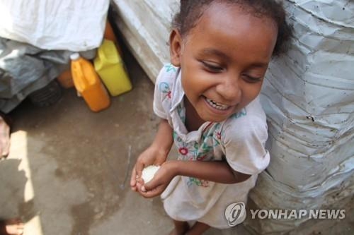 This undated photo, provided by the World Food Program (WFP), shows a Yemeni child holding rice sent from South Korea. (PHOTO NOT FOR SALE) (Yonhap)