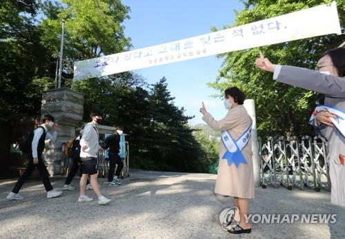 Teachers instruct students to maintain social distancing in front of Cheongun Middle School in Seoul on May 27, 2020. South Korea implemented the second phase of school reopenings the same day, affecting the two lowest grades of elementary school, kindergarten students, middle school seniors and second-year high school students. (Yonhap)