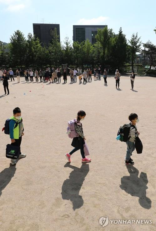 Students keep a distance from one another after arriving at Cheongun Elementary School in Seoul on May 27, 2020, amid the coronavirus pandemic. (Yonhap)