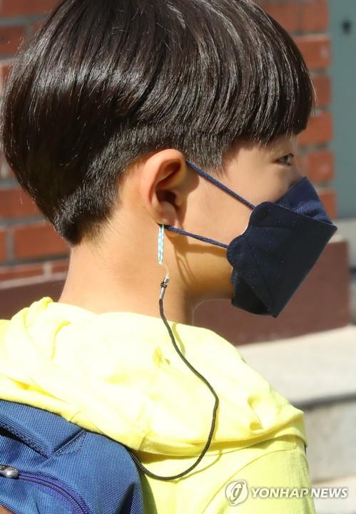 A pupil has his face mask attached to a string around his neck, to prevent him from losing it, at Ochi Elementary School in the southwestern city of Gwangju on May 29, 2020, amid the coronavirus pandemic. (Yonhap)