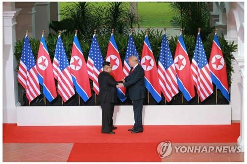 This photo, taken from the North's Rodong Sinmun daily newspaper on June 13, 2018, shows North Korean leader Kim Jong-un (L) shaking hands with U.S. President Donald Trump before a row of their national flags ahead of a summit on the Singaporean resort island of Sentosa a day earlier. (For Use Only in the Republic of Korea. No Redistribution) (Yonhap)