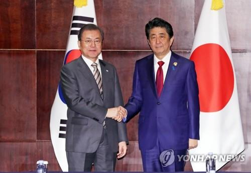 South Korean President Moon Jae-in (L) shakes hands with Japanese Prime Minister Shinzo Abe ahead of their summit talks in Chengdu, southwestern China, on Dec. 24, 2019. (Yonhap)