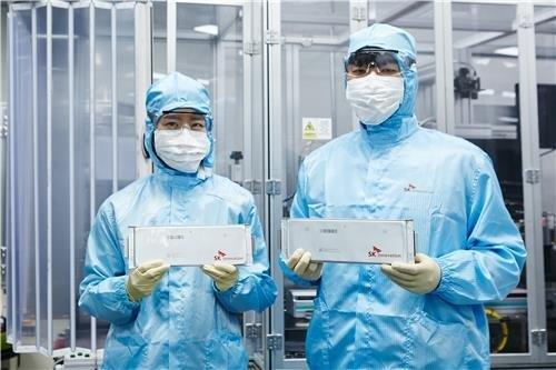 This file photo, provided by SK Innovation Co., shows its researchers holding battery cells for electric vehicles. (PHOTO NOT FOR SALE) (Yonhap)
