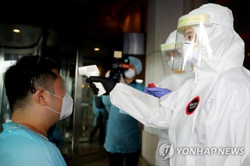 In this photo taken by the Joint Press Corps on Aug. 5, 2020, a health worker checks the body temperature of an arrival at a shelter in Incheon. (Yonhap)