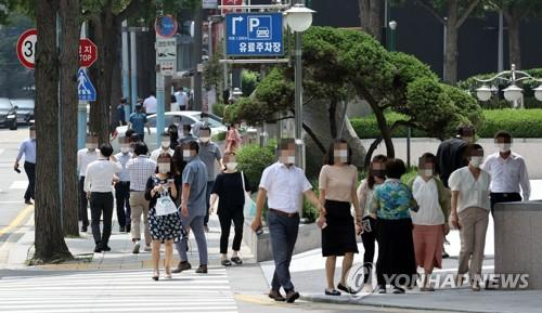 Citizens wearing protective masks walk on a street in central Seoul on Aug. 18, 2020. (Yonhap)