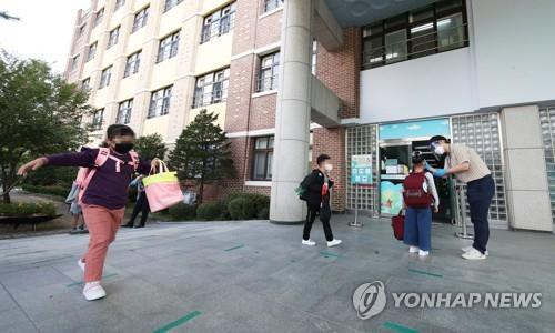 A child gets her temperature checked before entering school in Suwon, south of Seoul on Sept. 21, 2020. (Yonhap)