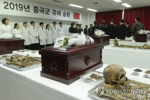 The file photo taken April 1, 2019, shows South Korean and Chinese officials holding a ceremony in Incheon, west of Seoul, to put the remains of Chinese soldiers killed in the 1950-53 Korean War into coffins for their repatriation. (Yonhap)
