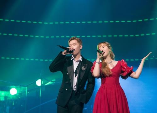 This photo, provided by YG Entertainment, shows AKMU's Lee Chak-hyuk (L) and his younger sister Su-hyun singing. (PHOTO NOT FOR SALE) (Yonhap)