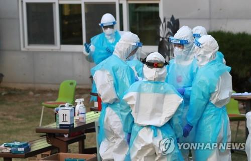 This file photo shows medical workers preparing to carry out coronavirus tests. (Yonhap)