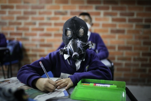 This photo, provided by Juancho Torres of Turkish newswire Anadolu Agency, shows a student in Colombia wearing a handmade gas mask in class. (PHOTO NOT FOR SALE) (Yonhap)