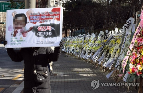The file photo shows a row of funeral wreaths made of white and yellow flowers laying alongside the wall of the Seoul Southern District Court to mourn the loss of a 16-month-old girl who was allegedly tortured to death by her adoptive parents. (Yonhap)