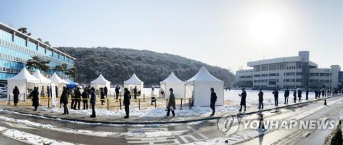 People stand in line to receive coronavirus tests at a makeshift clinic at the Gyeonggi provincial government building in Suwon, south of Seoul, on Jan. 13, 2021. (Yonhap)