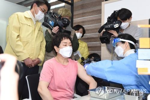 A 61-year-old health care worker from a nursing facility receives the country's first COVID-19 vaccine at a public health center in Seoul on Feb. 26, 2021. (Yonhap)