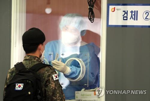A service member undergoes a COVID-19 test at a temporary testing site in front of Seoul Station in central Seoul on April 5, 2021. (Yonhap)