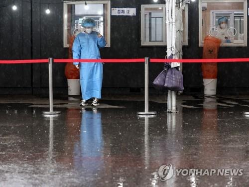 Medical workers wait for visitors to receive coronavirus tests at a makeshift clinic in front of Seoul Station on May 4, 2021. South Korea's daily new virus cases bounced back to the 500s the same day amid growing fears that rising cases of COVID-19 variants could become another challenge to the country's virus battle. (Yonhap)