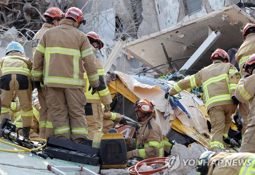 Firefighters rescue people trapped under a mound of debris in the southwestern city of Gwangju on June 9, 2021. (Yonhap)
