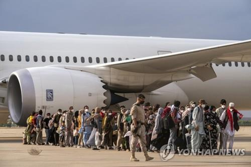 This AP photo shows Afghan people who were transported as part of the evacuation process from Afghanistan walking after disembarking a plane at the Torrejon military base in Madrid on Aug. 23, 2021. (Yonhap)
