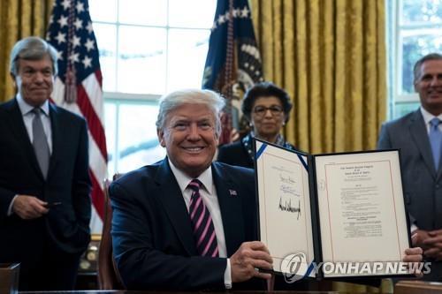 지난 3월 코로나19 예산 서명하는 트럼프 대통령 [UPI=연합뉴스]