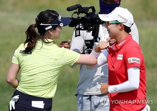 팔꿈치 인사를 나누는 유소연(왼쪽)과 김효주.