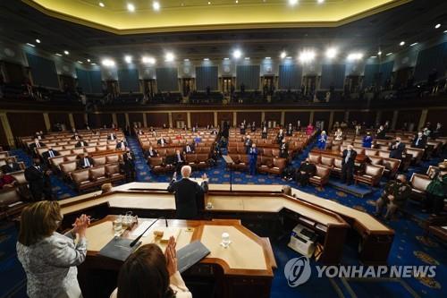 바이든 대통령 연설 중 기립박수 치는 민주당 의원들(오른편)과 착석해 있는 반대편 공화당 의원들.[EPA=연합뉴스]