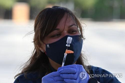 23일(현지시간) 미 캘리포니아 LA의 한 임시 백신 클리닉에서 간호사가 화이자의 코로나19 백신을 준비하고 있다. [AFP=연합뉴스]