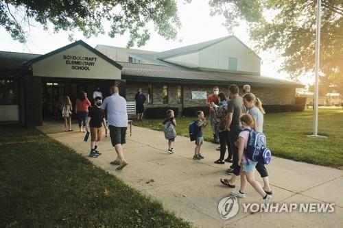 30일(현지시간) 개학한 미 미시간주의 스쿨크래프트 초등학교에 학생과 학부모들이 등교하고 있다. [AFP=연합뉴스]