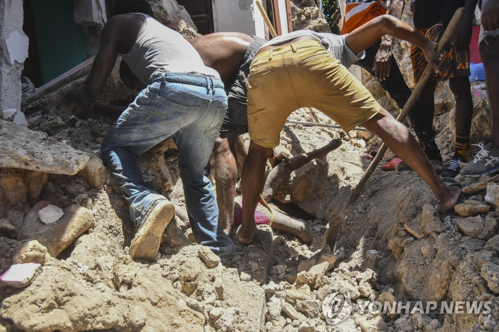 아이티 강진 후 잔해에 깔린 이들을 구조하고 있다.