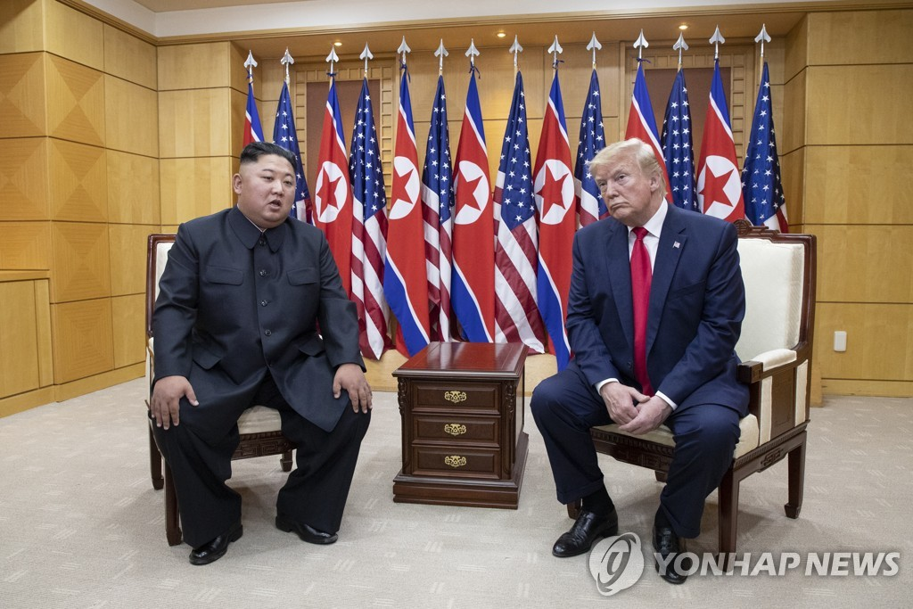 This photo, taken June 30, 2019, shows U.S. President Donald Trump (R) and North Korean leader Kim Jong-un holding talks at the inter-Korean border truce village of Panmunjom. (Yonhap)