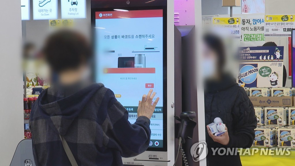 This image provided by Yonhap News TV shows people using kiosk machines at a store. (PHOTO NOT FOR SALE) (Yonhap)