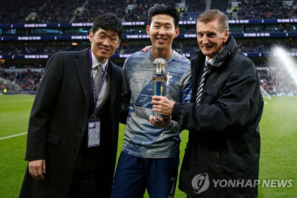 박지성(왼쪽)으로부터 'AFC 올해의 국제선수상' 트로피를 받은 손흥민(가운데)